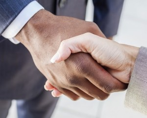 Two suited people shaking hands celebrating business continuity | Kerry London team