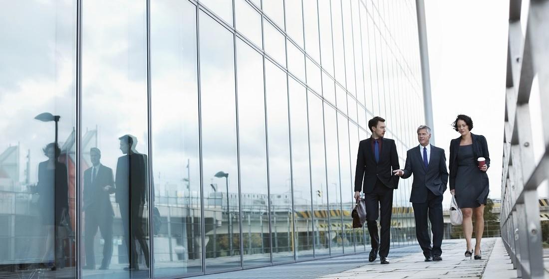 professionals walking alongside glass building