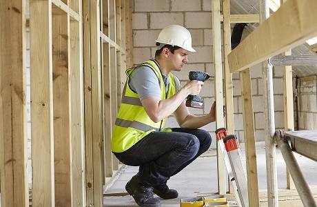 construction worker working on stud partitions representing builders insurance