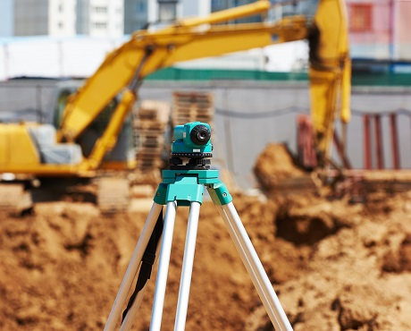 Surveying tool in front of construction site representing civil engineering contractors