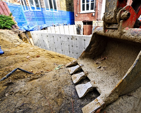 Basement being constructed with digger in foreground representing contract works insurance