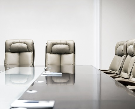 Chairs arranged around a board room table representing Directors and Officers insurance