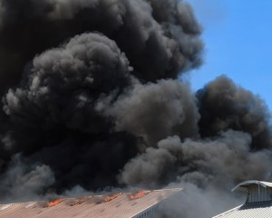 black smoke rising above a burning building representing Loss Assessors Fee Indemnity Insurance