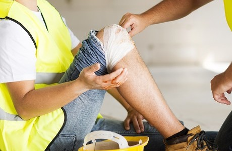 tradesman with injured knee being cared for representing Personal accident insurance