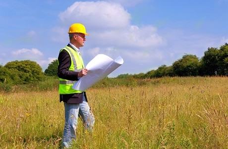 Architect in a field looking at architectural plans representing Restrictive Covenants Indemnity Insurance