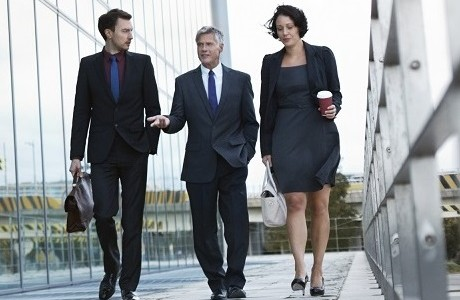 Three businesspeople walking and talking next to an office building representing professional associations